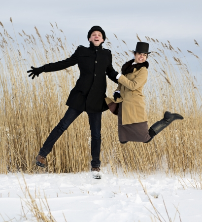 Man and woman jump on frozen lake beach photo