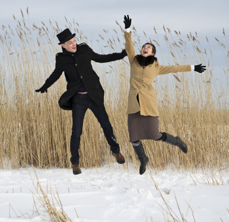 Happy man and woman jump on lake beach Stock Photo - 17785488