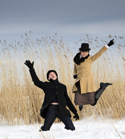 Man and woman posing near winter lake beach photo