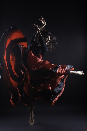 Young woman dance on one leg spanish flamenco