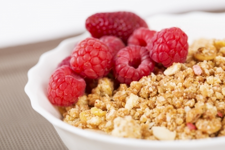 zoomed in: Zoomed berries on golden cereals in white bowl Stock Photo