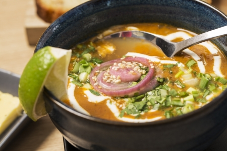 zoomed in: Zoomed bowl with soup and spoon in it Stock Photo