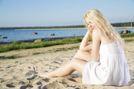 Woman in white dress indulgence on warm beach photo