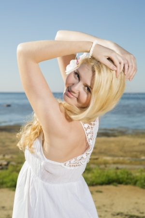 Smiling youthful woman in dress at sea background photo