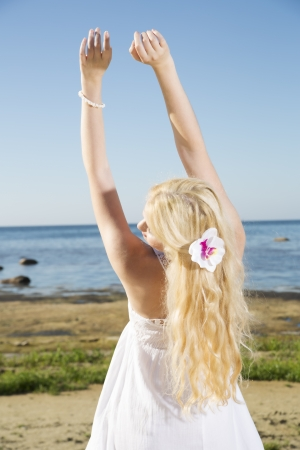 Young woman stretches long hands to blue sky photo