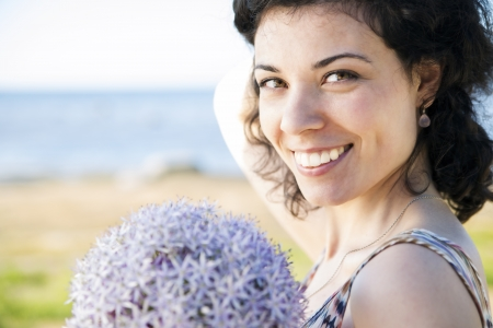 Happy woman with dark hairs posing with flower photo