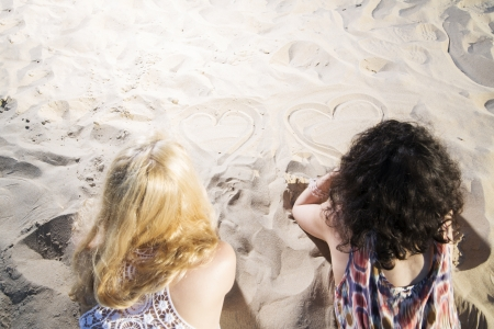 Two young womans draw hearts on warm sand photo