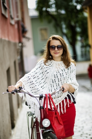 zoomed: Zoomed happy woman on city street with bicycle