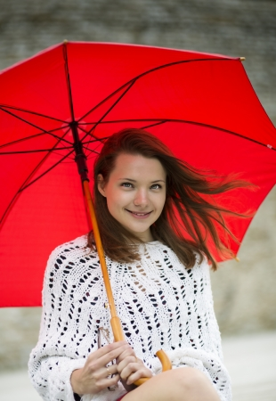 Smiling young woman with open umbrella at hand photo