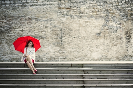 Happy woman sit with open umbrella at steps