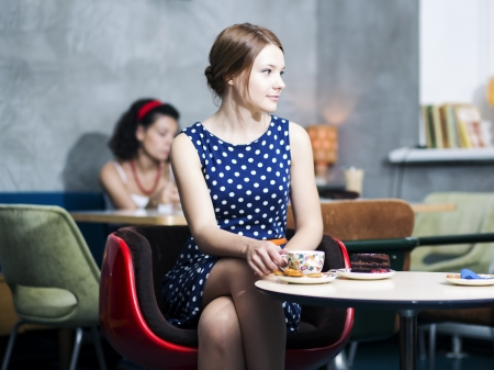 Zoomed woman in spotted dress sit in cafe photo