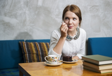 Woman eat cake with great pleasure  at cafe photo