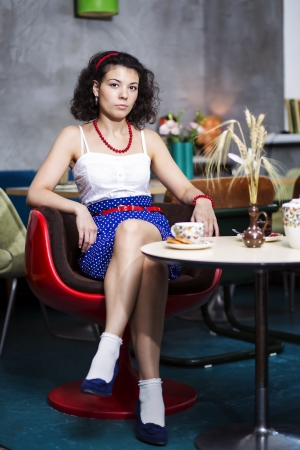 evaluative: Woman in café with evaluative look on face