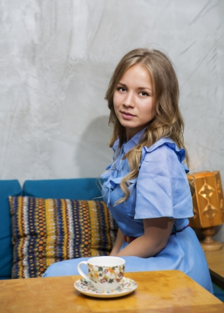 Woman at blue dress sit at squared table photo