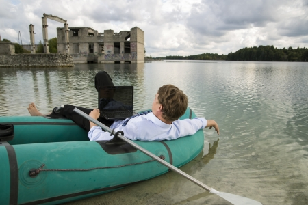 beardless: Dressed man lay over boat on lake shore Stock Photo