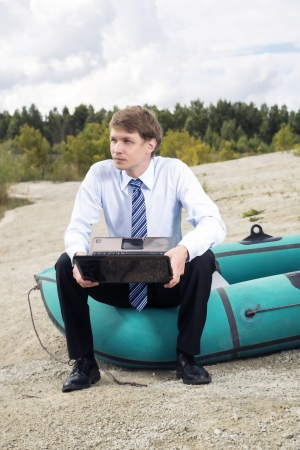 Dressed man sit on boat edge with laptop photo