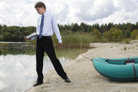 Dressed man plan drags boat at lake surface photo