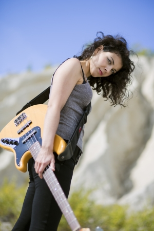 nice looking: Nice looking young woman posing with yellow guitar Stock Photo