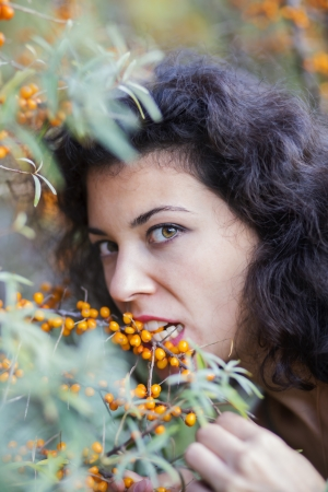 zoomed: Zoomed view of woman bite gooseberries from branch Stock Photo