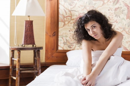 restless: Woman stretches herself in bed after restless night Stock Photo