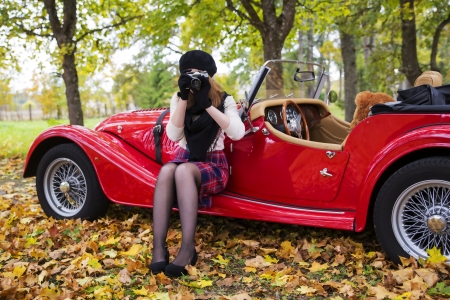 Young woman take picture with car on background photo
