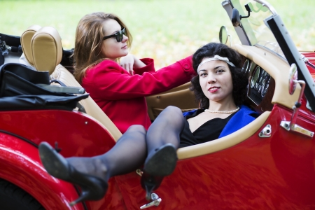 Young women take vocation ride on red car photo