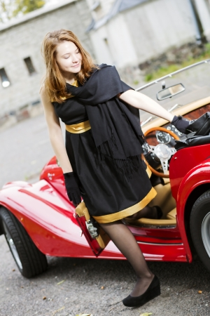 Satisfied woman in black come out from car photo