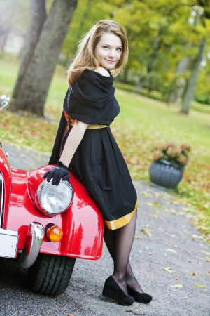 Happy woman in black and retro car headlight photo