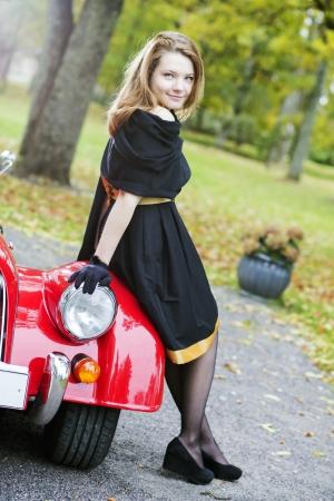 Happy woman in black and retro car headlight