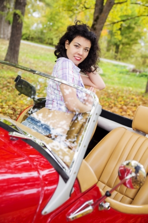Woman at retro car on passanger leather seat photo
