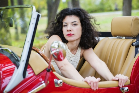 Serious look woman look out of retro car photo