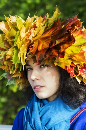 suspiciously: Woman with maple leaves on head look suspiciously