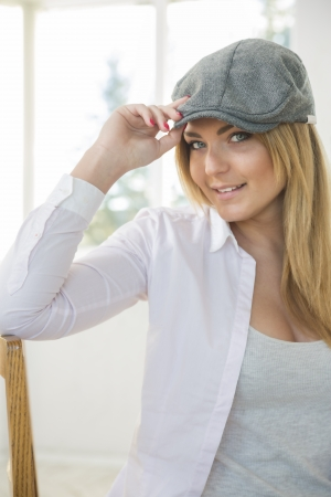 Young woman on chair with stylish grey hat photo