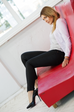 imitation leather: Woman on low red sofa from imitation leather