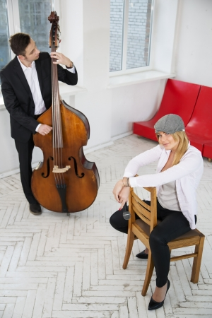 Woman sit backwards on chair and man play photo