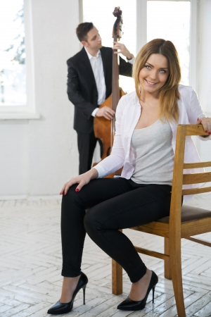 Happy woman on wooden chair and contrabas player photo