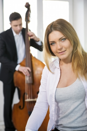 White dressed woman and contrabas player on background photo