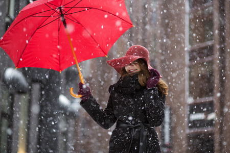Woman with umbrella on snowy street at day