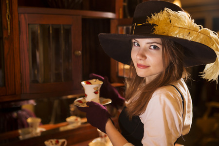Zoomed woman at fashioned dress with porcelain cup photo