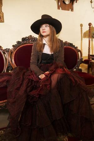 Woman at lush fashioned dress and renaissance furniture photo