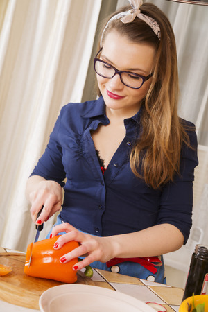 Woman at sexy suit cuts paprika to pieces photo