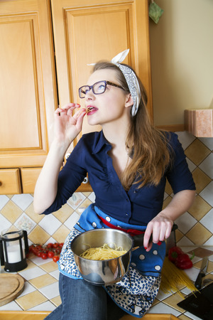 eating noodles: Woman at sexy suit eating noodles from saucepan Stock Photo