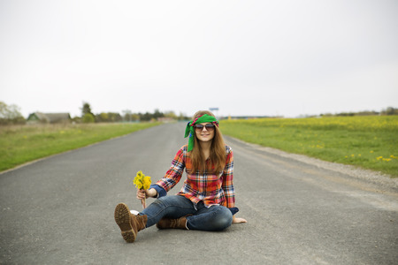 Young woman with yellow flowers on asphalt road photo
