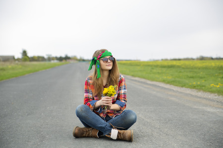 Young woman dreaming with yellow flowers at hands photo