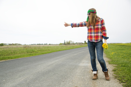 Young woman vote on road with yellow flowers photo