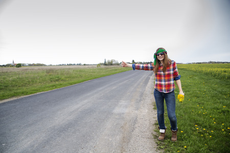 Young woman vote on empty road with flowers photo