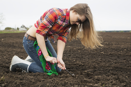 black soil: Young woman dig up from cultivated black soil Stock Photo