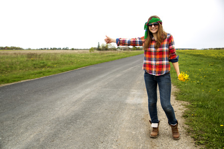 Young woman vote on road with finger up photo