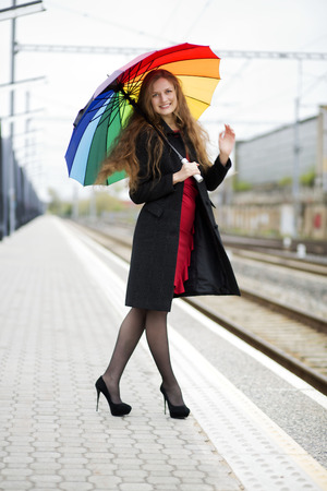 Woman with rainbow umbrella at hand welcomes observers Stock Photo