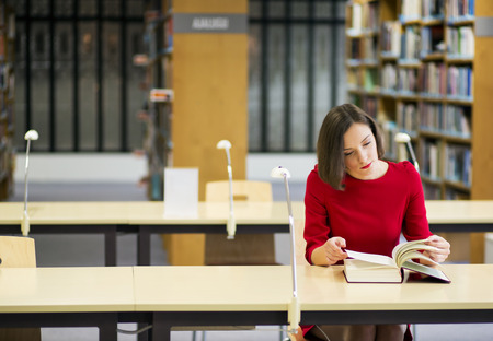 Young woman in library seek knowledge from book Stock Photo